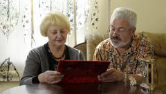 Retired couple looking at an album indoor Stock Footage