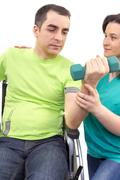 Physical therapist works with patient in lifting hands weights. - stock photo