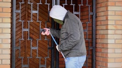 Robber with crowbar near the gates - stock footage