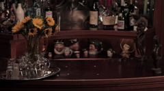 Dolly Zoom of Liquor Bottles and Statue Bust at Bar Stock Footage