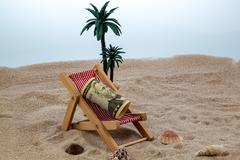 deck chair with piggy bank and dollars - stock photo