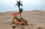 Deck chair with piggy bank and dollars Stock Photos