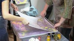 People printing Ebru drawing from water on silk shawl. Ebru is water marbling Stock Footage