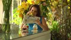 Young woman reading newspaper by dinning table at home HD Stock Footage
