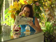 Young woman reading newspaper by dinning table at home NTSC Stock Footage