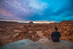 Girl looking at sunset sky over the goblin valley Stock Photos