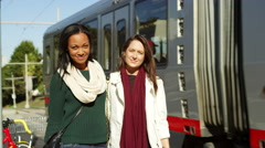 Two girl friends hug and smile at the camera as a tram passes behind them Stock Footage
