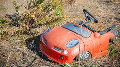 trash in shantytown - child car - stock photo