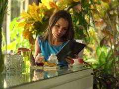 Young woman sitting with tablet during breakfast by dinning table NTSC Stock Footage