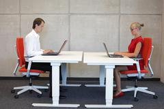 Business couple in correct sitting posture at workstations Stock Photos