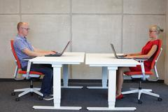 Man and woman  in correct sitting posture at workstations in office Stock Photos