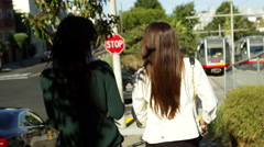 The camera follows two girls walking down a hill in California during the day in Stock Footage