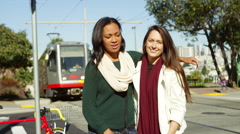 Two girl friends hug and smile at the camera as a trolley passes behind them Stock Footage