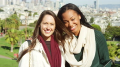 Two women stand on top of a hill in a park and smile into the camera Stock Footage