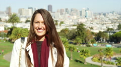 Portrait of a young woman standing on top of a hill in a park with the city Stock Footage