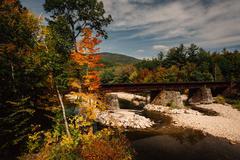 train bridge over a river and autumn color near bethel, maine. - stock photo