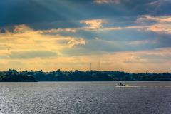crepuscular rays over the back river seen from cox point park, essex, marylan - stock photo