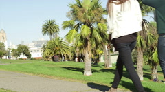 Two friends walk through the park on a sunny day Stock Footage