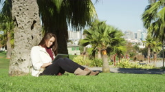 A young woman sits in the grass under a tree in a park and uses her tablet Stock Footage