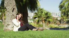 A young woman answers her cell phone while sitting under a tree in a park - stock footage