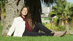 A young woman smiles while sitting in the grass, under a tree in a park Stock Footage