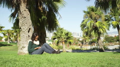 A young woman sits under a tree in the park and meets a friend Stock Footage