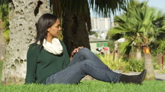 A young woman sitting in the grass, under a tree in a park during the day smiles Stock Footage