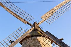 Old wooden mill against the blue sky - stock photo