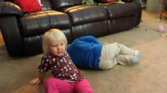 Boy and girl wrestle on floor - stock footage