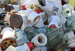 Insulators of electrical wires in glass and ceramics in a landfill Stock Photos