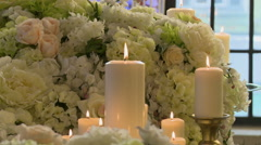Lighted candles on backdrop of white flowers Stock Footage