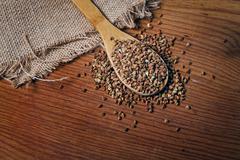 buckwheat groats and wooden spoon - stock photo