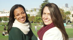Two girl friends hanging out in the park during the day, look into the camera Stock Footage