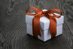 gift box with ribbon bow on old oak table - stock photo