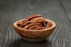 Pecan nuts in olive wood bowl on oak table Stock Photos