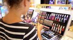 Young Woman Testing Cosmetics in Beauty Shop in Shopping Center. - stock footage