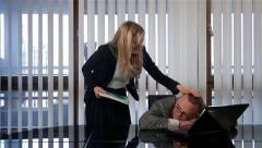 Funny scene. Male manager sleeping at work and female boss kisses him to wake up Stock Footage