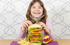 Happy little girl with big hamburger Stock Photos