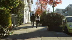 Slow motion shot of two girl friends walking up a hill, away from the camera Stock Footage