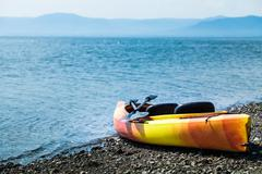 Orange and Yellow Kayak With Oars on the Sea Shore - stock photo