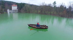 Flying around person rowing towards flooded castle Stock Footage