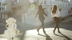 Slow motion shot of two girl friends walking down the street during the day Stock Footage
