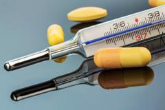 clinical thermometer and pills - stock photo