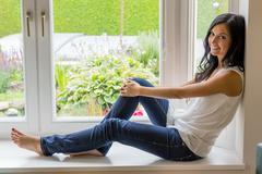 Woman sitting by the window Stock Photos