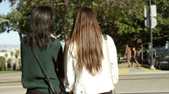 Two friends wait on the corner before crossing the street Stock Footage