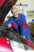 Woman as a mechanic in auto repair shop Stock Photos