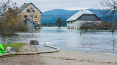 Fire hose squirt water in to flooded village Stock Footage