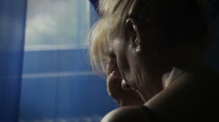 upset woman deep in her problems near the window: desperation, sadness - stock footage