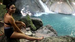 Woman in retro swimsuit resting on the shore of the waterfall Stock Footage