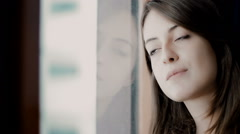 Thoughtful young woman: cute girl stay pensive at the window Stock Footage